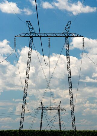 over voltage: High voltage electricity pylons and power lines over blue sky and white clouds