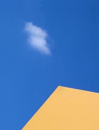 meta: Yellow meta lroof over blue sky and cloud