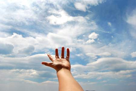 whitw: Open hand over blue sky and whitw clouds Stock Photo
