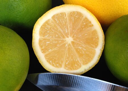 squeeze shape: Cuted lemon,limes and knife on black background