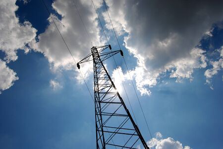 over voltage: High voltage electricity pylon over blue sky and white clouds and sun Stock Photo