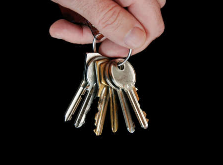 Hand with keys on black background photo