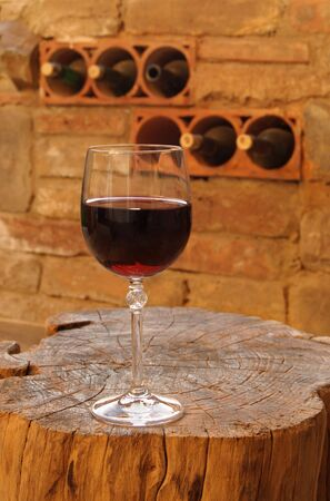 Glass of red wine on rustic wooden table in winery Stock Photo