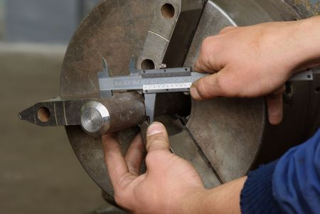 Close up of measuring metal part on lathe with caliper photo