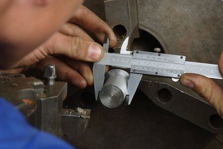 Close up of measuring metal part on lathe with caliper Stock Photo