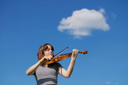 Young girl playing violin over blue sky and cloud photo