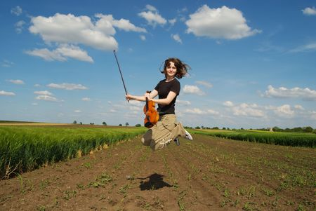 Teenage girl with violin jumping in field Stock Photo