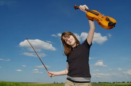 Teenage girl with violin  over blue sky and clouds photo