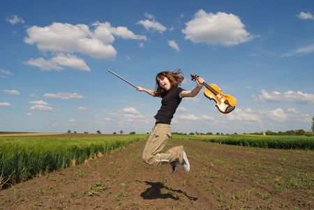 Teenage girl with violin jumping in field photo