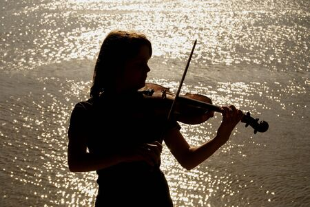 Silhouette of teenage violin player over sunset on river,lake or sea
