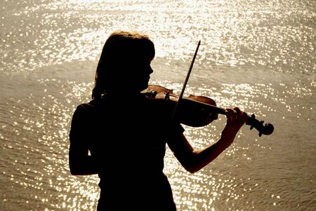 musician silhouette: Silhouette of teenage violin player over sunset on river,lake or sea