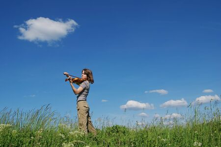 violin player: Young girl playing violin over blue sky and clouds on meadow Stock Photo