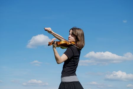 Young girl playing violin over blue sky and clouds photo