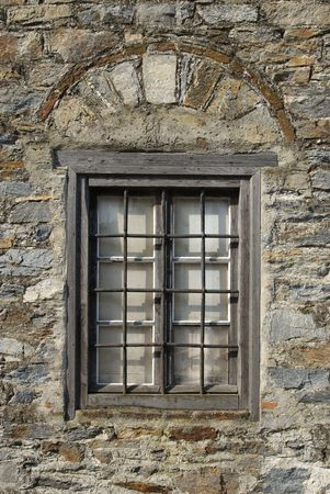 Window on old stone house in Greece with metal lattice photo