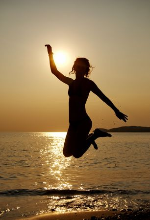 Silhouette of a young jumping girl in sunset on seaside Stock Photo - 3454335