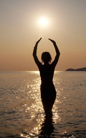 Silhouette of a young beautiful girl in sunset on seaside photo