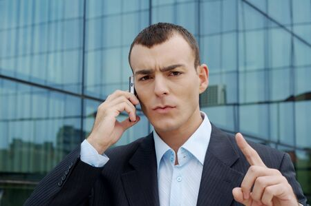 Young serious business man phoning in front of building Stock Photo - 3823479