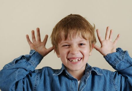 Young caucasian gesturing boy in blue shirt photo
