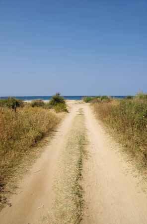 Empty road to the seaside with blue sky photo