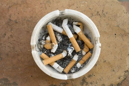 White ashtray full of cigarette on tile background photo