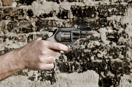 Human hand holding toy gun with brick wall in background photo