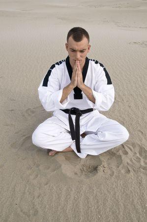 Young man marshal art master meditating  at sand photo