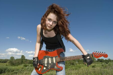 Red hair teenage girl with red electric guitar  photo