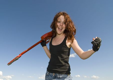 Red hair teenage girl with red electric guitar and blue sky photo