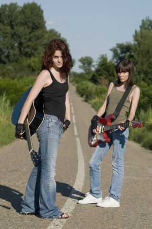 Two young girls with guitars on the road photo