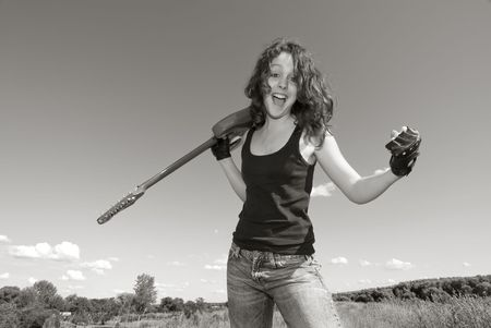 Teenage girl with  electric guitar in field with clear  sky photo