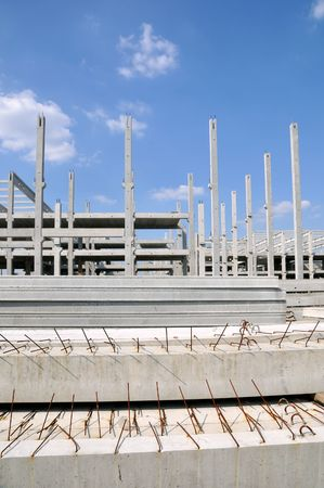 Concrete construction and beams with blue sky and clouds photo