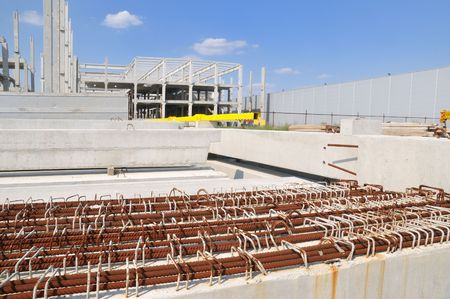 Concrete construction and reinforcement with blue sky and clouds photo