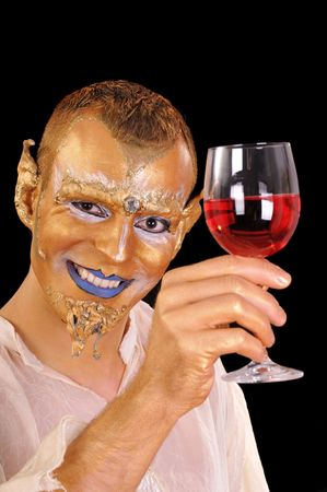 Young smiling artistic painted man with glass of beverage photo