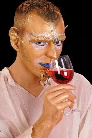 Young mystic artistic painted man with glass of beverage photo