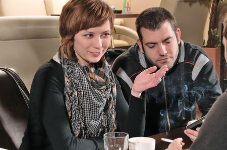 Young people sitting in cafe and talking photo