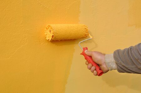 yellow wall: Painting of orange wall with paint roller Stock Photo