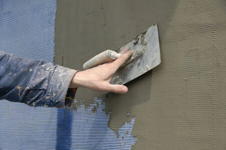 stucco facade: Trowel spreading mortar  on insulation of wall