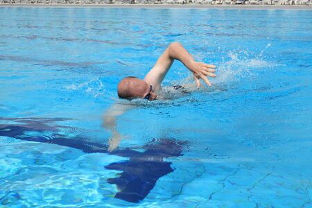 Caucasian man with glasses swimming in pool photo
