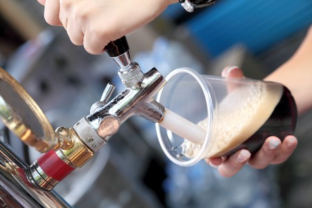 Pouring dark beer to plastic glass from beer tap Stock Photo