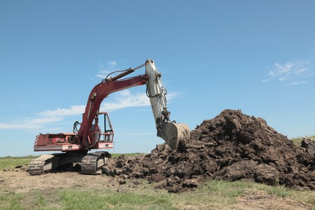 dirt pile: Excavator at meadow with heap of ground