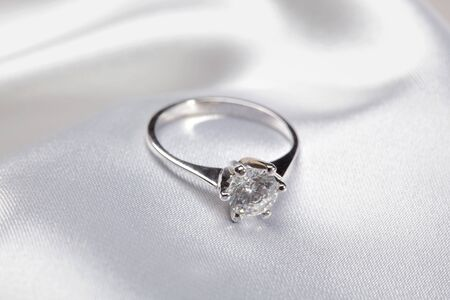 Close up photo of platinum or silver ring on white textile  Stock Photo