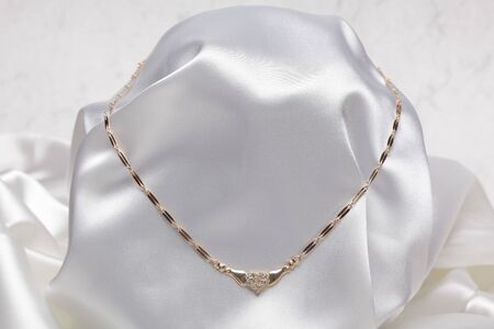 Close up photo of gold necklace on white textile  photo
