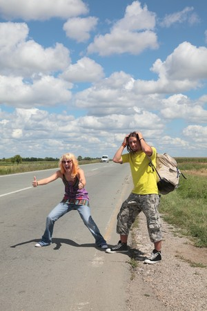 Caucasian smiling  girl and boy gesturing and hiking at a road photo