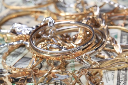 golden bracelet  and other jewelry at money background