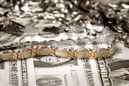 golden bracelet and other jewelry at money background photo