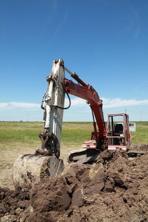 Old excavator at meadow with heap of ground photo
