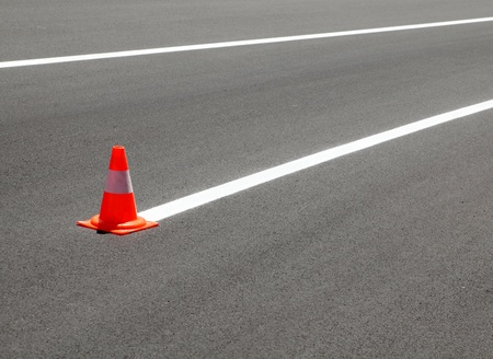 Fresh painted line at asphalt road and traffic cone photo
