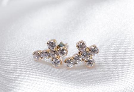 golden cross ear rings on white textile background photo