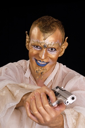 Young artistic painted man with pistol photo