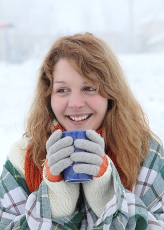 Beautiful smiling teenage girl in a cold winter day with cup of tea or coffee photo